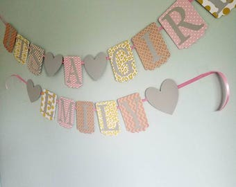 It's a girl banner and a name banner for baby shower decorations. Pink, gold, white, and gray baby shower decor