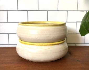 Pair of vintage white bowls with yellow edge.