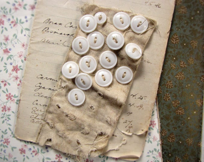 antique white glass buttons on a scrap of shabby cloth - sewing or assemblage supply