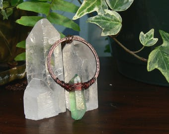 copper + quartz // wire-wrapped iridescent green coated quartz point. hammered copper circle. earthy.