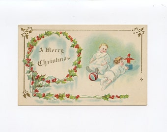 Vintage Christmas Postcard Babies Playing With Christmas Toys Holly Wreath Red Berries by Samuel Gabriel Embossed Used Abby Hosmer ~ 7437Pb