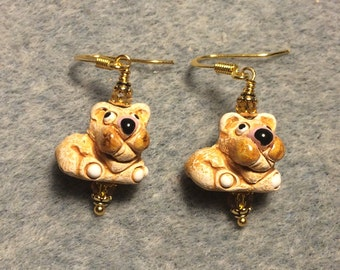 Small tan and brown ceramic bulldog bead earrings adorned with amber Chinese crystal beads.