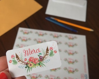 """Stickers """"MERCI"""" with flowers on white paper"""
