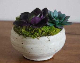 Artificial succulent arrangement in clay planter