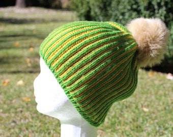 Green and gold handknitted beanie in super fine Australian merino wool with faux fur pompom