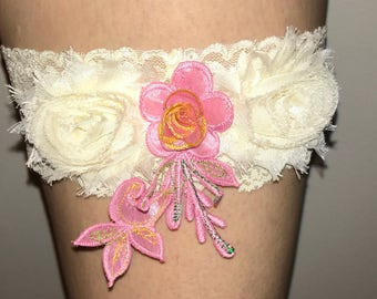 Wide ivory lace garter with double ivory flowers and adorned with a pink flower appliqué
