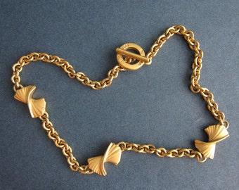 Nina Ricci, ras neck metal with 3 knots.