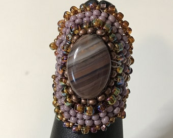 Natural oval agate stone with purple accents.