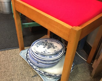 Utility stool upholstered in red fabric