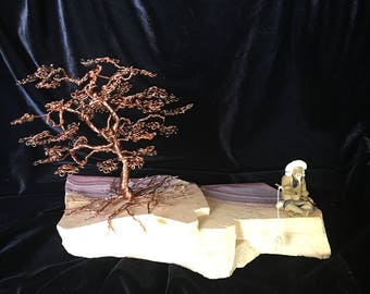 Wire wrapped copper wire tree mounted on rock with fishing Mudman figurine