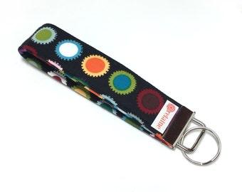 Colorful sprockets keychain, key fob, key wristlet, key holder, key chain.  Colorful sprockets on black.  Fabric keychain wristlet.