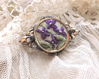 Victorian brooch with ribbon work in center
