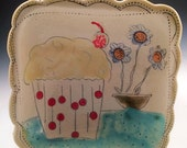 Cupcake dish with white bottom and red polka-dots handmade out of porcelain.