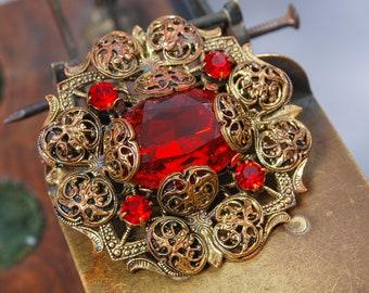 Vintage brass filigree brooch, with red glass rhinestones.