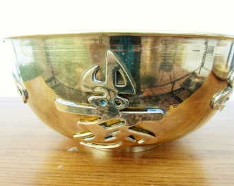 Very large Asian brass bowl with symbols.