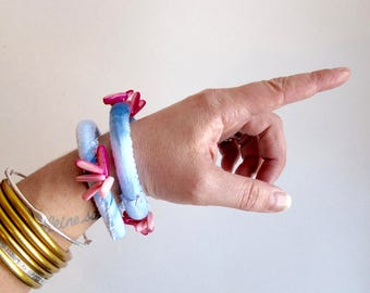 Shibori fabric bracelet with pink shell beads hand dyed indigo and stitched on cotton fabric with pink stitching An Astrid Endeavor Spring