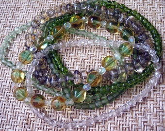 Bracelets, Stretch Magic Style, in Purples and Greens, 14 in all