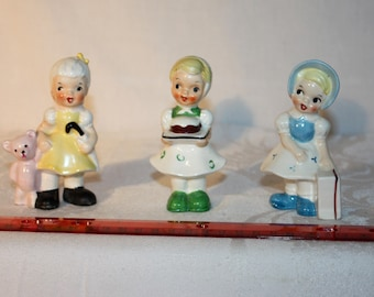3 young lady figures by Ucagco Ceramics, Japan. One has a cake on a tray, one has a suitcase, and one has a teddy bear