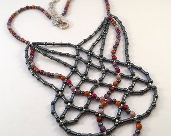 Bib style necklace - 4mm round beads of hematite, plus reds, pinks and purples.