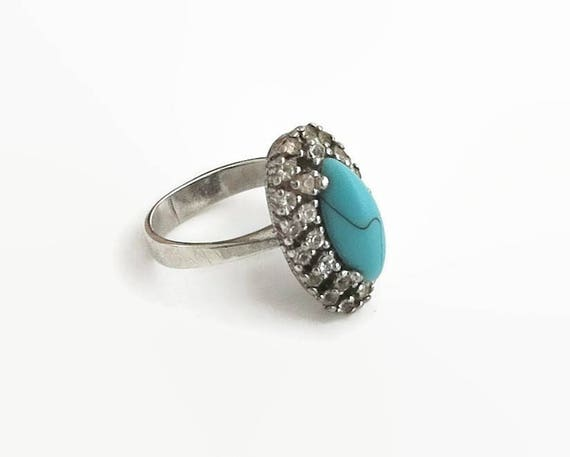 Sterling silver, turquoise, and rhinestone ring with oblong shaped turquoise surrounded by 2 rows of clear rhinestones, stamped 925, 1970s