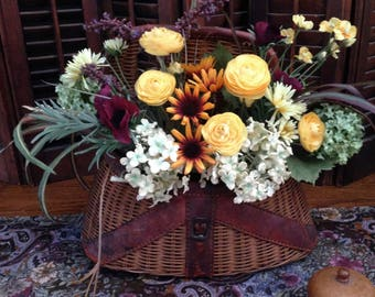 Country floral arrangement in vintage fishing creel. Charming cottage or cabin decor.