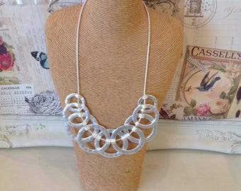 Silver coloured necklace with circular detail