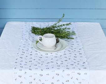 Handmade white linen table runner with small blue anchors