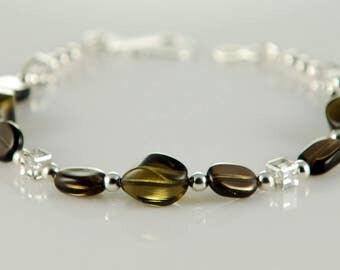 Bracelet of Smokey quartz, Swarovski crystals, silver plated beads on a Sterling silver chain.