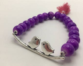 Two Little Birds & a Branch Charm on Pink Splattered Purple beaded flexible bracelet with Pink Tassel.