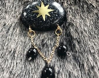Black and gold atomic starburst glitter resin bead drop brooch.