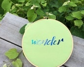 "Embroidered ""wander"" in blue ombre on light green background"