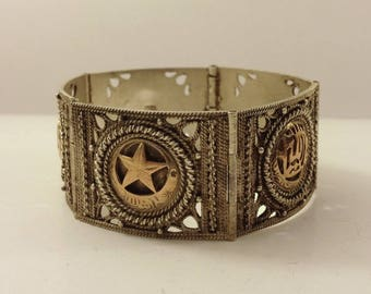 1920's, silver hinged round bracelet with a temple motif