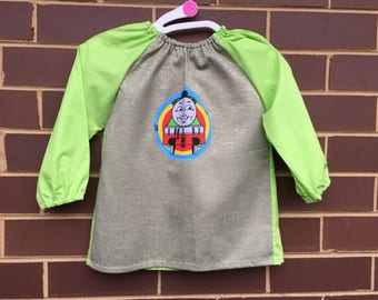 Toddler's long sleeve waterproof art smock, age 2-3 years. Green, lime green with train motif.