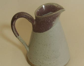 Stoneware jug with speckled white and red glaze.