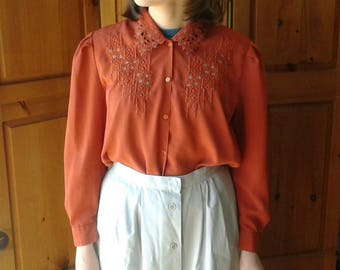 Vintage burnt orange secretary blouse with floral embroidery and cutout collar