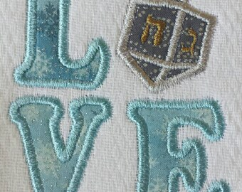 Beautiful dreidel inside the word Love. This unisex design is great for a boy or girl. Available as a bib, burp cloth, body suit or t shirt.