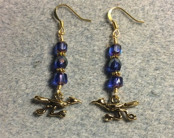 Gold roadrunner charm earrings adorned with bright blue Czech glass beads.