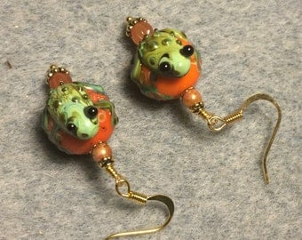 Orange and green lampwork frog bead earrings adorned with orange Czech glass beads.