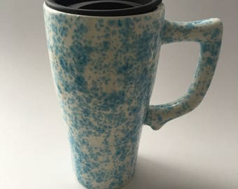 Ceramic travel mug hand with handle decorated with a light blue mottled design