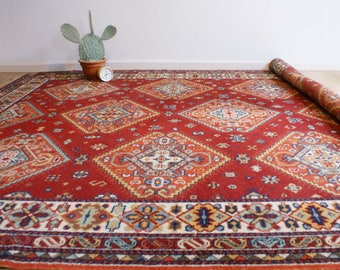 Vintage carpet with Bohemian/Oriental atmosphere. Big red retro dress with flowers and a little bird
