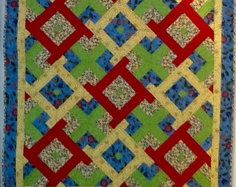 Quilt of primary colors (plus green) make this bright and showy.  Just right to catch the eye and interest of a baby or toddler.