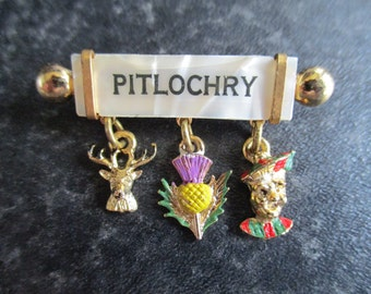 Vintage Mother Of Pearl PITLOCHRY SOUVENIR Bar BROOCH featuring a Stag, Thistle and a Scottish laddie.