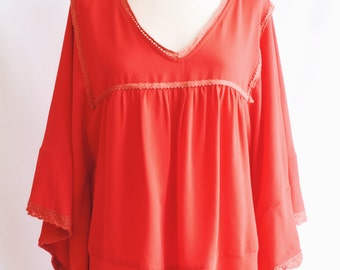Red Poncho style blouse.