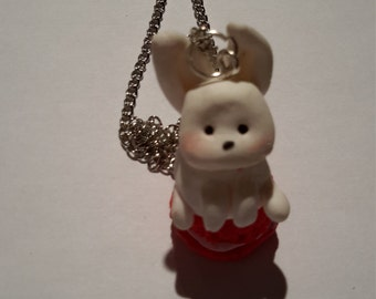 Rabbit necklace in fimo sitting on a macharon