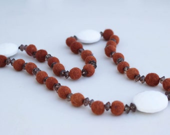 Long necklace made of felt, beads, beads and white medallions.