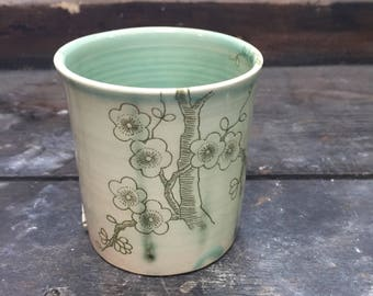 Cup turned, stoneware, oxides décor, cherry blossoms, under enamel green type celadon.