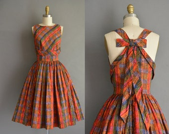 50s open back with a large bow detail vintage dress by Julie Clark.  vibrant paisley print dress. vintage 1950s dress