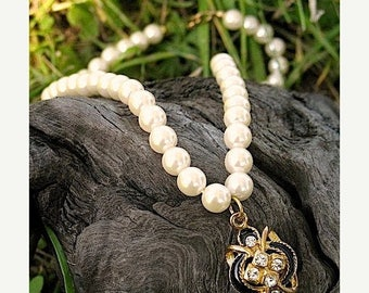 This is a Romantic Victorian Style Faux Pearl Necklace With A Gold Medallion With Black Enameling and  Rhinestones  in MInt Circa 1960s