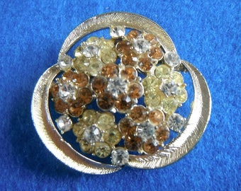 Round and sparkling brooch with citrus, clear and orange sparkling stones