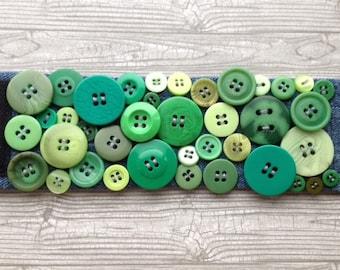 Handmade green button cuff bracelet on denim